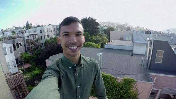Man takes a selfie on rooftop, with a view of San Francisco's mission district in background Royalty-free stock video