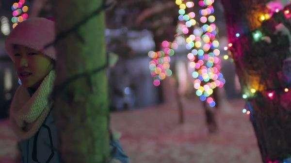 0710ffbf60faa Playful little girl dressed in santa hat runs through colorful lit winter  wonderland