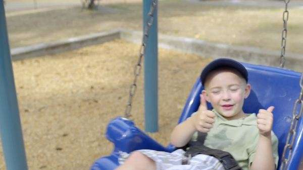 Happy little boy swings in park, gives two thumbs up Royalty-free stock video