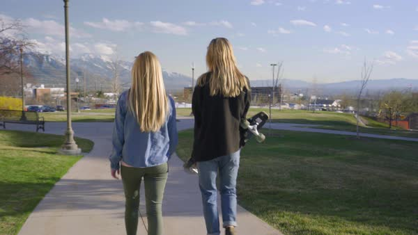 Friends go for a walk on school campus, girl carries her skateboard Royalty-free stock video
