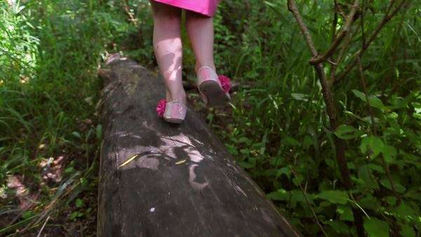 Little girl explores the forest, walks down a log, away from camera. close-up of her legs, slow motion Royalty-free stock video