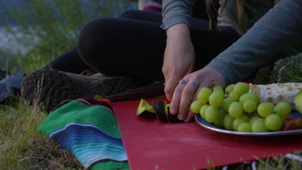 Closeup Of Young Woman Slicing An Avocado, Shares A Slice With Her Friend, Enjoying A Picnic In Nature Royalty-free stock video