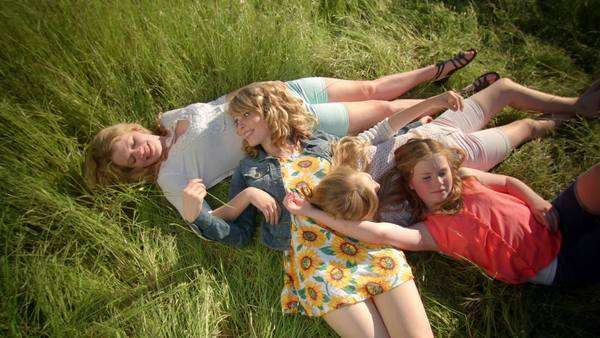 Birds eye view of girls laying in field, they tickle each other and play with each other's hair Royalty-free stock video
