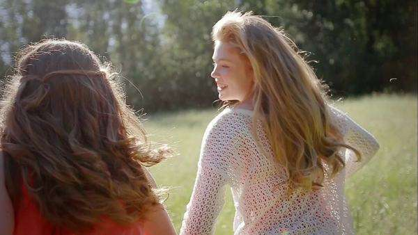 Sisters hold hands and run in slow motion through beautiful meadow Royalty-free stock video