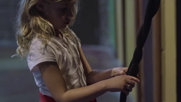 Little girl practices braiding technique on rope, she concentrates hard Royalty-free stock video