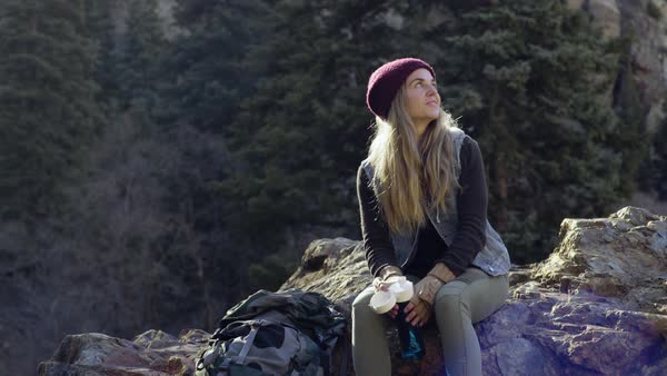 Adventurous Young Female Backpacker Rests On A Boulder, Takes A Water Break And Enjoys Views Royalty-free stock video