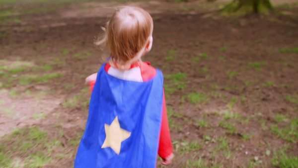 Little boy runs around a park in his superhero cape Royalty-free stock video