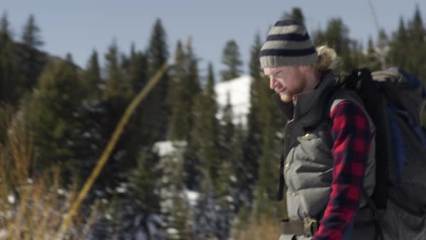 Camera Pans From Right To Left With Backpacker Snowshoeing, His Friend Follows Behind Royalty-free stock video