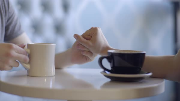 Closeup Of Cute Couple Reaching Across Table To Hold Hands, They Cheers With Their Free Hands Royalty-free stock video