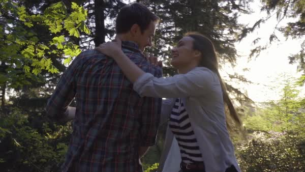 Young Woman Surprises Her Boyfriend, Then Gives Him A Kiss, Takes His Hand And Leads Him Through Forest, Running (Slow Motion Steadicam Shot) Royalty-free stock video