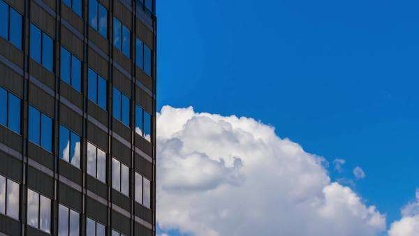 Timelapse of clouds reflecting in the windows of a tall business building Royalty-free stock video