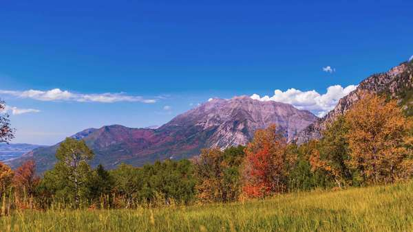 Timelapse pan across this fall mountain scene in beautiful 4K as clouds move and form above the mountains. Royalty-free stock video
