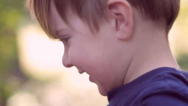 Little blond boy with big blue eyes having fun and hugging his 30 something working father outside with soft focus hand held shot. Royalty-free stock video