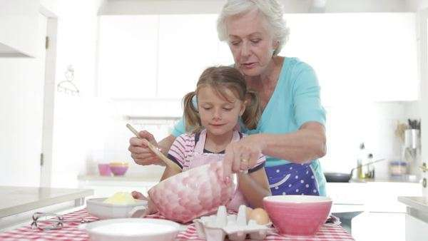 Grandmother reads recipe before showing granddaughter how to mix ingredients together which she then copies. Royalty-free stock video