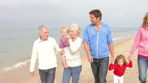 Family group walking towards camera along autumn beach with grandparents carrying youngest grandchild. Royalty-free stock video