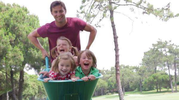 Father pushes 3 children towards camera in wheelbarrow - sequence changes to slow motion as they approach camera. Royalty-free stock video