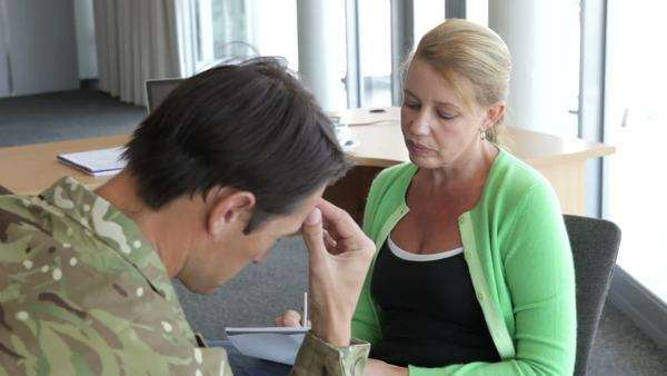 Soldier discussing problems with counsellor who listens and takes notes. Royalty-free stock video