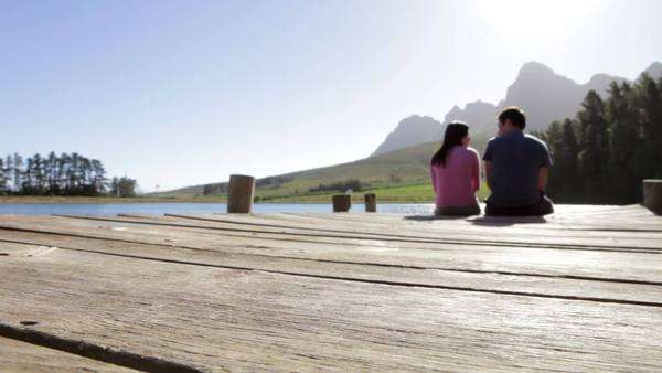 Romantic young couple sitting on a wooden jetty by a lake viewed from behind. Royalty-free stock video