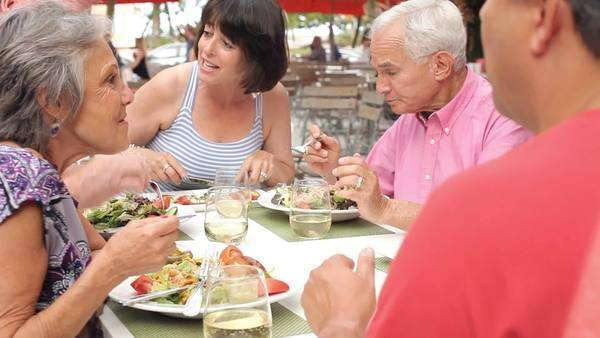 Camera tracks around group of happy seniors enjoying meal at outdoor restaurant. Royalty-free stock video