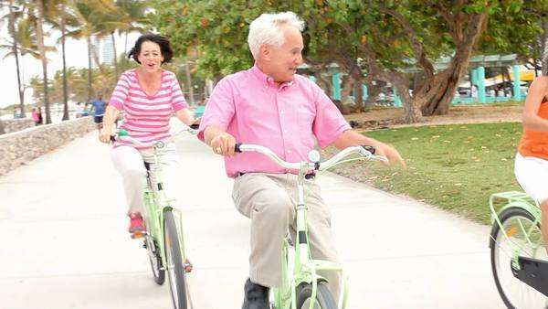 Group of seniors riding bucycles towards camera through park. Royalty-free stock video