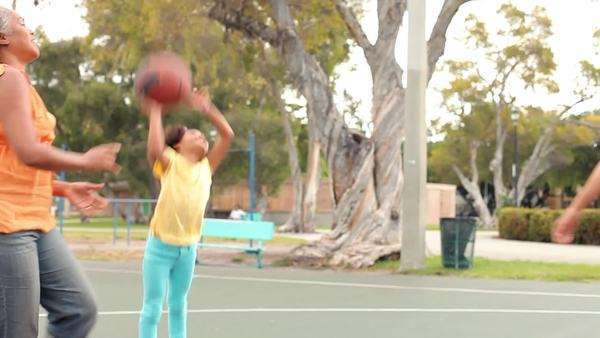 Multi-generation family playing basketball on outdoor court,. Royalty-free stock video