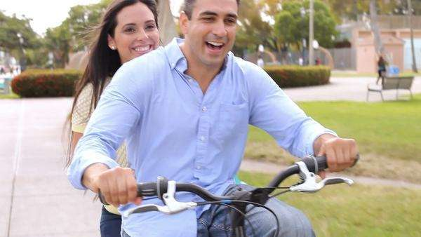 Happy couple sharing bike as they cycle through park towards camera. Royalty-free stock video