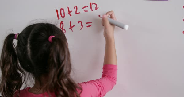Elementary schoolgirl doing maths on whiteboard, back view Royalty-free stock video