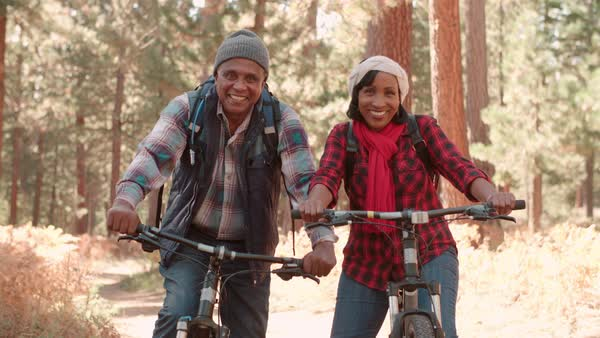 Senior couple sitting on bikes in a forest, close up Royalty-free stock video