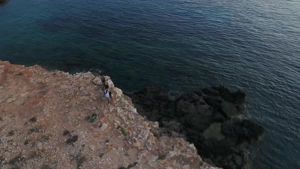 Aerial shot of friends on cliffs watching sun set over sea Royalty-free stock video