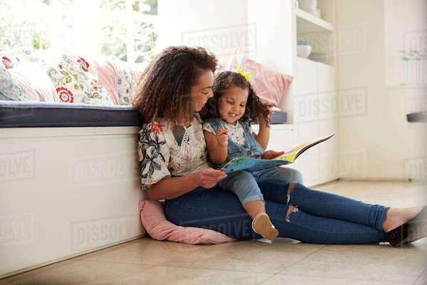Mother sitting on the floor reading a book with her daughter Royalty-free stock photo