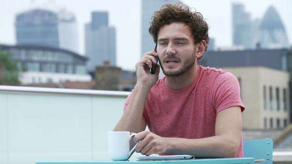 Young man sitting on roof terrace with urban skyline in background, using mobile phone. Royalty-free stock video
