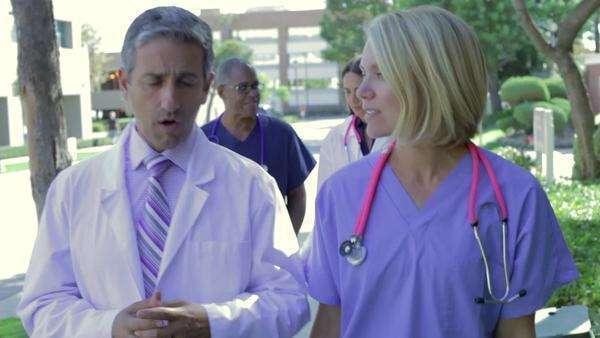 Four members of medical team walking towards camera in hospital grounds talking. Royalty-free stock video