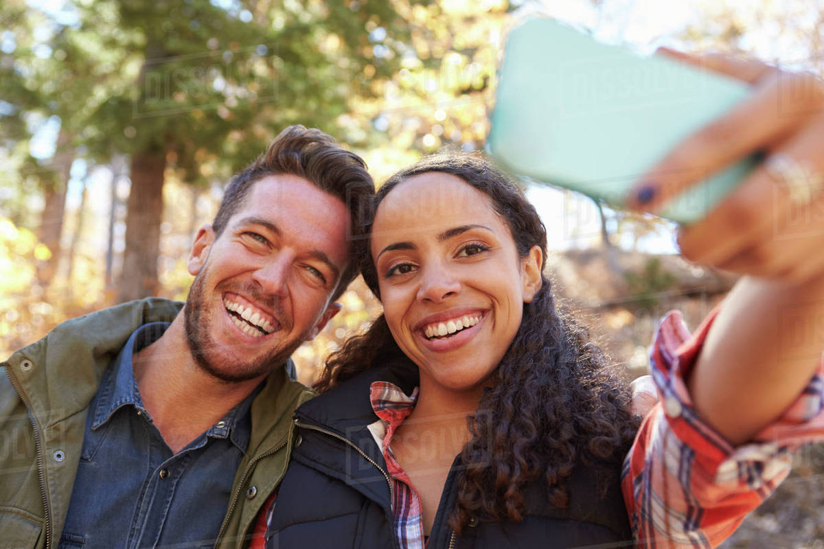 laughing mixed race couple taking a selfie in a forest stock photo