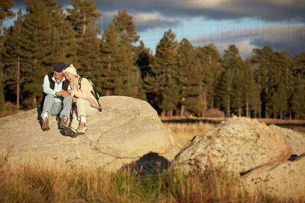 Senior couple sit on a rock near a forest, California, USA Royalty-free stock photo