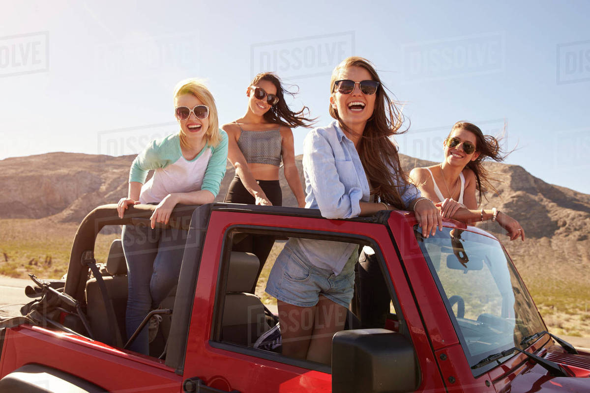 Four Female Friends On Road Trip Standing In Convertible Car Stock Photo Dissolve