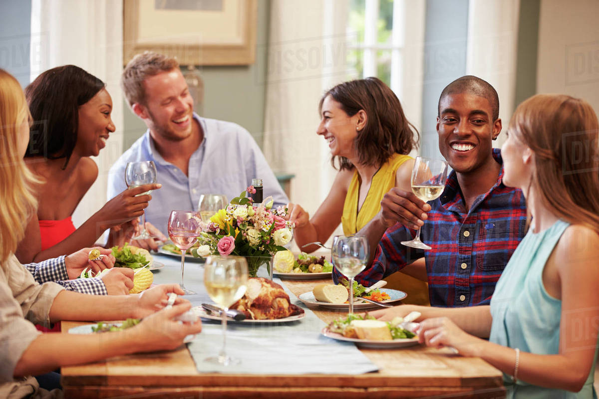 friends at home sitting around table for dinner party stock photo dissolve. Black Bedroom Furniture Sets. Home Design Ideas