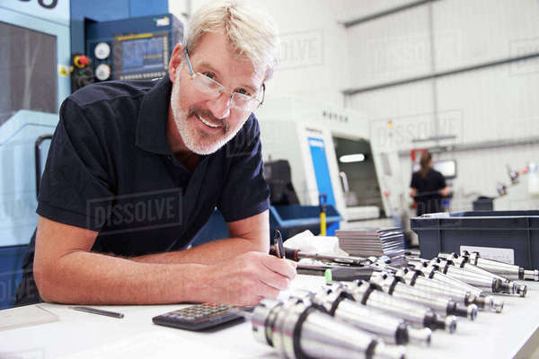 Engineer planning project with cnc machinery in background Royalty-free stock photo