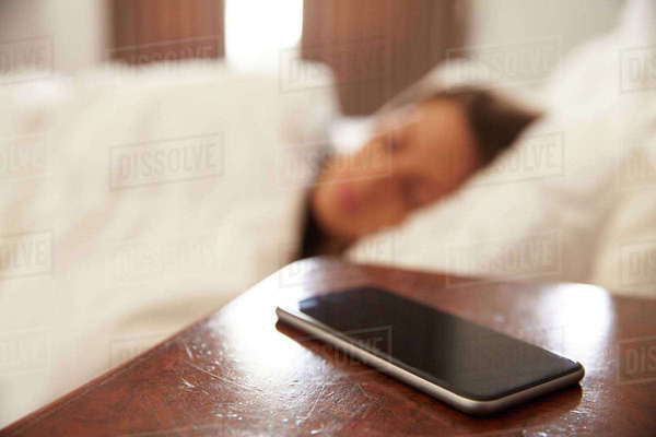 Woman asleep in bed with mobile phone on bedside table Royalty-free stock photo