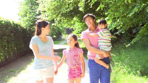 Asian family walking along summer countryside path in slow motion. Royalty-free stock video