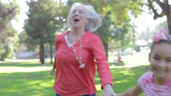 Granddaughter holding hands with grandmother and encouraging her to run through the park. Royalty-free stock video