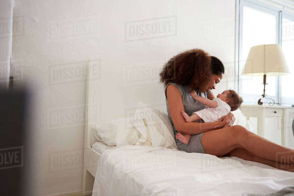 Mother Cuddling Baby Daughter In Bedroom At Home Royalty-free stock photo
