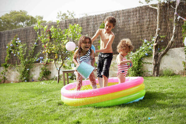 Children Having Fun In Garden Paddling Pool Royalty-free stock photo
