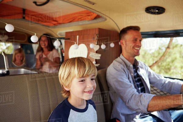 Dad driving family in a camper van, with son up front Royalty-free stock photo