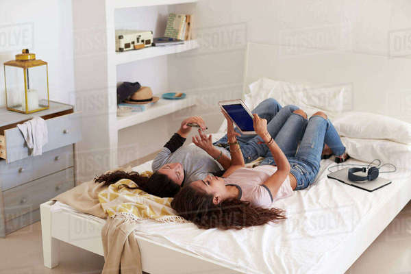 Two girls lying on bed using phone and tablet, elevated view Royalty-free stock photo