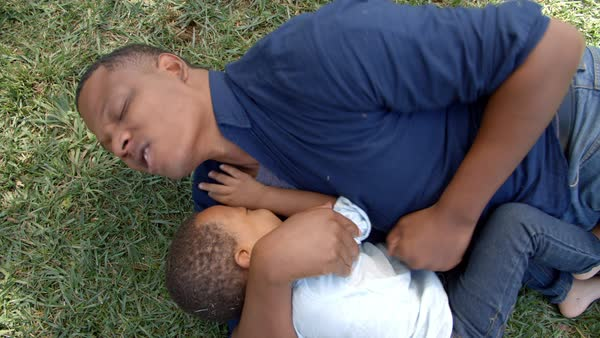 Father play fighting with young son in park Royalty-free stock video