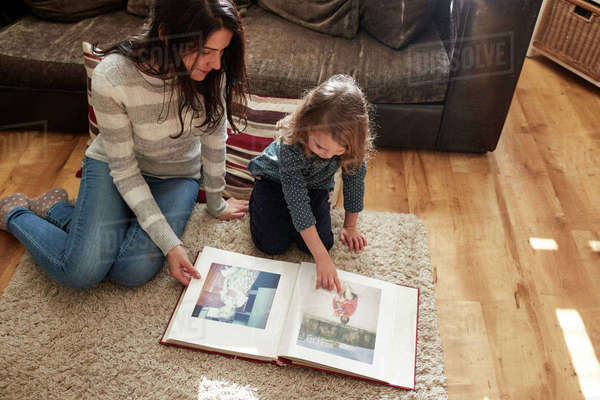 Mother and daughter at home looking through photo album Royalty-free stock photo