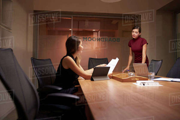 Businesswoman stands talking to colleague working late Royalty-free stock photo