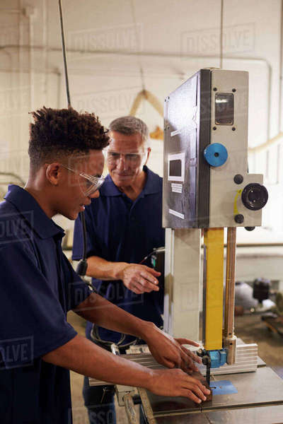 Carpenter training male apprentice to use mechanized saw Royalty-free stock photo