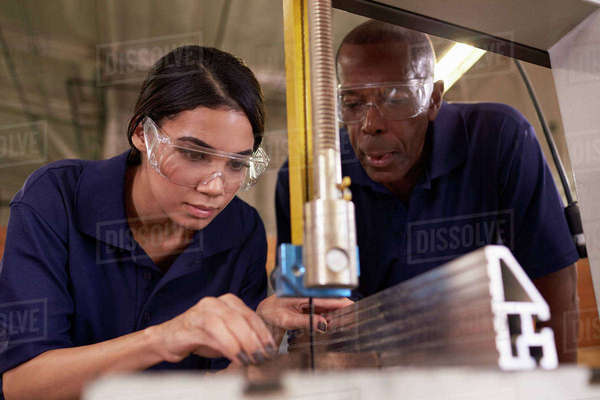 Carpenter training female apprentice to use mechanized saw Royalty-free stock photo