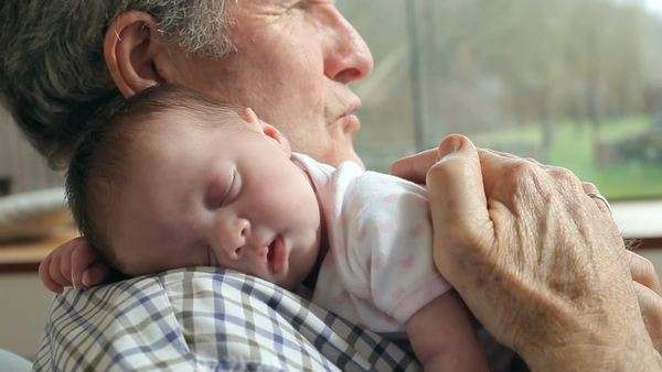 Close up of grandfather cuddling newborn baby granddaughter. Royalty-free stock video
